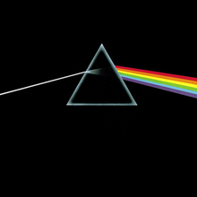 A small grey equilateral and hollow triangle sits slightly above the centre of an opaque black image. A perfectly straight light-grey line enters from the middle of the left edge of the image, and is angled slightly upward to meet the left side of the triangle. Inside the triangle the grey line expands slightly, fading to black as it reaches the centre. On the right side of the triangle a thick bar composed of red, orange, yellow, green, blue, and violet angles downward to the middle right edge of the image.